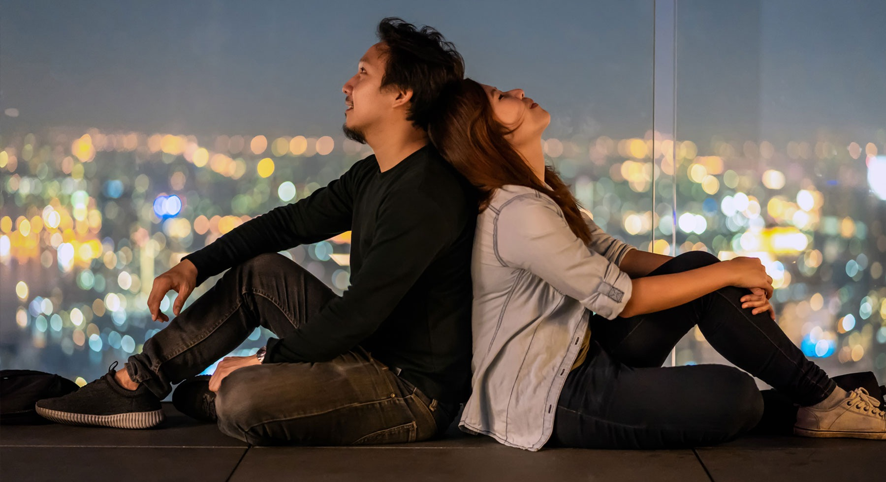 lifestyle image of a couple sitting against each other with the lights of a city in the view
